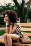 A beautiful girl is sitting on a park bench on a background of g Stock Photo