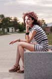A beautiful girl is sitting on a park bench on a background of g Royalty Free Stock Photos