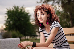 A beautiful girl is sitting on a park bench on a background of g Royalty Free Stock Image