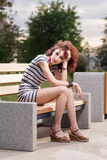 A beautiful girl is sitting on a park bench on a background of g Royalty Free Stock Photo
