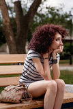 A beautiful girl is sitting on a park bench  Royalty Free Stock Images