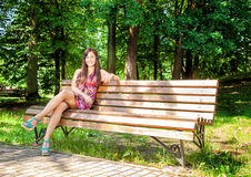 Beautiful girl sitting on a park bench Stock Photo