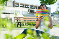 Beautiful girl sitting in park and hiding with notebook. Beautiful young girl sitting in park and hiding with notebook having fun with copy advertising area royalty free stock photos