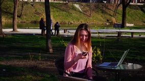 Beautiful girl sitting in park with laptop and speaking by smartphone. stock video