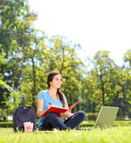 Beautiful girl sitting in park and writing Royalty Free Stock Image