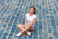 Beautiful girl sitting on the pavement Royalty Free Stock Image