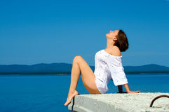 Beautiful girl sitting on the pier Royalty Free Stock Photo