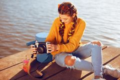 Beautiful girl sitting on the pier near the river. Beauty model with brunette hair. The girl at hot sunny day taking pictures old royalty free stock photo