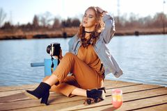Beautiful girl sitting on the pier near the river. Hipster model in choker with blond cerly hair. The girl at hot sunny day taking royalty free stock images