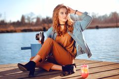 Beautiful girl sitting on the pier near the river. Hipster model in choker with blond cerly hair. The girl at hot sunny day taking royalty free stock image