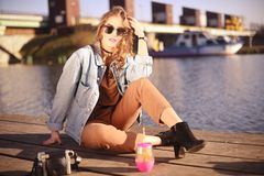 Beautiful girl sitting on the pier near the river. Hipster model in sunglasses with blond cerly hair. The girl in the denim jacket royalty free stock photos
