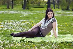 Beautiful girl sitting on the plaid in the park Royalty Free Stock Image