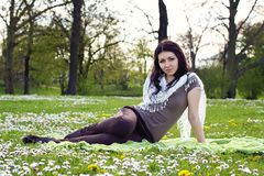 Beautiful girl sitting on the plaid in the park Royalty Free Stock Photography