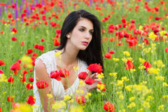 Beautiful girl sitting in the poppy field Stock Images
