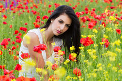 Beautiful girl sitting in the poppy flower field Stock Photography