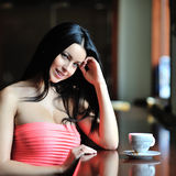 Beautiful girl sitting at the restaurant with a cup of tea or co Stock Photo