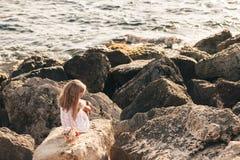 Beautiful girl sitting on rocky seashore Stock Images