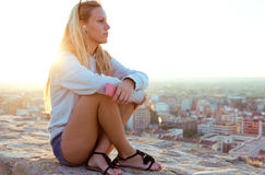 Beautiful girl sitting on the roof and listening to music. Stock Photography