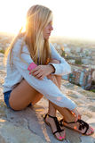 Beautiful girl sitting on the roof and listening to music. Royalty Free Stock Photo