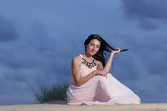Beautiful girl sitting on a sand dune Royalty Free Stock Images