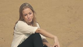 Beautiful girl sitting on the sand and flirting stock video