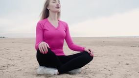 Beautiful girl sitting on sand in Lotus position. closes his eyes, takes breath. stock video