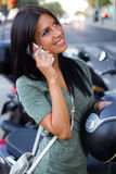 Beautiful girl sitting on a scooter and talking with phone. Stock Photo
