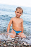 Beautiful girl sitting at the seashore Royalty Free Stock Photography