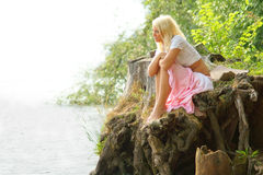 Beautiful girl sitting at shore and looking away. Young pretty caucasian blond woman sit at river bank or lake shore and looking away. Girl looking on the copy Stock Image