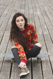 Beautiful girl sitting on skateboard, urban lifestyle concept. Royalty Free Stock Images