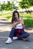 Beautiful girl sitting on skateboard and use mobile phone stock image