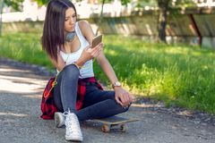 Beautiful girl sitting on skateboard and use mobile phone. Outdoors, urban lifestyle stock image