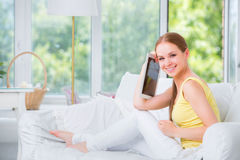 Beautiful girl sitting on a sofa against the window and shows the electronic tablet Royalty Free Stock Photography
