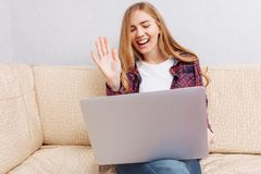 Beautiful girl sitting on the sofa at home, with a laptop, communicating with loved ones on Skype, is welcome royalty free stock images