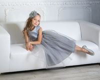 Beautiful girl is sitting on the sofa Stock Photo
