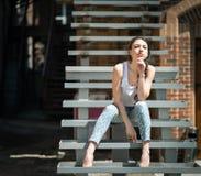 Beautiful girl sitting on stair. Stock Photo