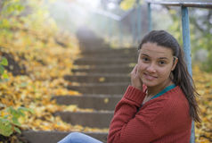Beautiful girl sitting on the stairs in autumn Stock Photos