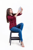 Beautiful girl sitting on a stepladder in the Studio and looks a. T the tablet. on white background. Made in Russia Royalty Free Stock Image