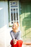 Beautiful girl sitting on steps of rural house Stock Images