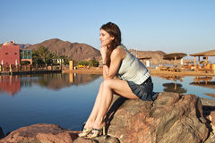 Beautiful girl  is sitting on the stone Stock Image