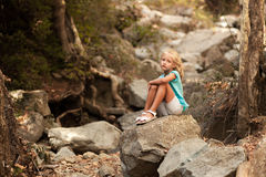 Beautiful girl sitting on the stone. In the foresf Stock Photos
