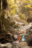 Beautiful girl sitting on the stone. In the foresf Stock Image
