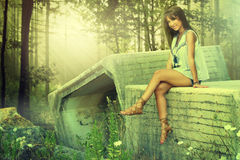 Beautiful girl sitting on a stone. On a forest Stock Photos