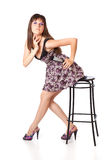 Beautiful girl is sitting on a stool Royalty Free Stock Photo