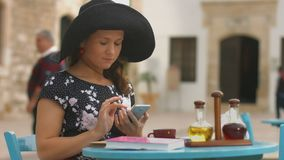 Beautiful girl sitting in street cafe, typing message, chatting on smartphone. Stock footage stock video footage