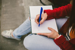 Beautiful girl sitting on the street with a notebook and pen in hand, making notes and rests. Royalty Free Stock Photography