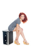Beautiful girl sitting on a suitcase Royalty Free Stock Images