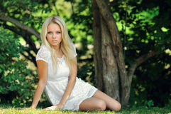 Beautiful girl sitting in a summer park Royalty Free Stock Photos