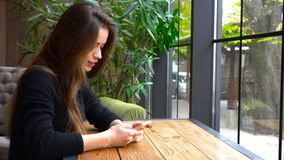 Beautiful girl sitting at a table looking into the phone and smiling stock video footage