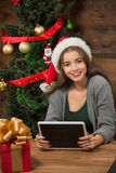 Beautiful girl sitting at the table with a tablet PC near New Year tree Stock Photography